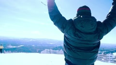 Young man snowboarder rises hands in Mountains in slowmotion on the sun Stock Footage