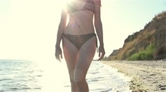 Girl walking in the sea at sunset. Slowmotion Stock Footage