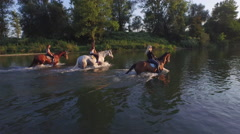 CLOSE UP: Three cheerful girlfriends riding horses in the river on sunny day Stock Footage