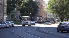 White bus and red-and-creamy tram pass a curve at Komsomola Street Stock Footage