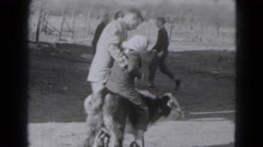 1947: the video shows a man trying to put his daughter to sit on a animal  Stock Footage