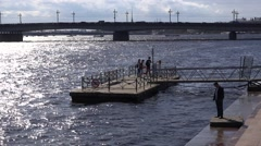Group of people at a boat pier at the Neva River against the sun Stock Footage