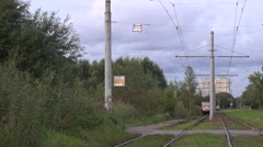 Tram runs along curvy worn-out tracks of a segregation along green in evening Stock Footage