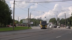 Modern single tram of route 23 and heavy truck turning along road curves Stock Footage