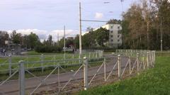 Tram runs in curve along single-track fenced segregation in Sosnovaya Polyana Stock Footage