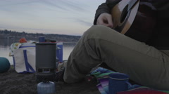 Man Plays Guitar On Sandy River Bank, While His Food Cooks On Small Camp Stove Stock Footage
