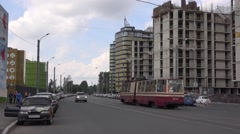 Old articulated tram passes along building site in Polyustrovo Stock Footage