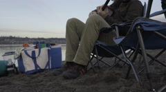 Man Sits In Camp Chair On Sandy River Bank, Plays Guitar Stock Footage