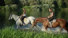 CLOSE UP: Two young girls riding horses along grassy river bank Stock Footage