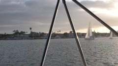 Sailing boats finish race in sun rays illuminating harbor 3 bimini supports i Stock Footage