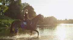 CLOSE UP: Young girls crossing wide river on horses on beautiful sunny day Stock Footage