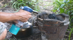 Man lighting charcol in stove Stock Footage