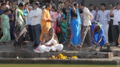 Man in white on Ram Kund ghat with pilgrims,Nashik,India Stock Footage