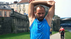 Young male jogger stretching arms in the city, super slow motion Stock Footage