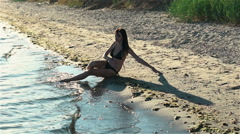 Young girl wets feet in sea water. Slowmotion Stock Footage