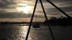 Sun setting passes through Bimini supports sunrays through clouds amazing pan Stock Footage