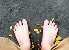 Bare foot on black stone and dried leaves Kuvituskuvat