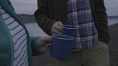 Closeup Of Couple On A Riverbank, They Cheers With Enamel Camping Mugs Stock Footage