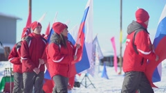 Russia, Novosibirsk, 2016: Athletes in winter clothes carry the Russian flag Stock Footage