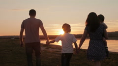 Happy family on sunset silhouette Stock Footage