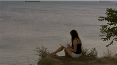 The woman relaxes and reads a book at the cliff above the sea Stock Footage