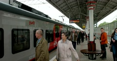 Red grey the train stops at the platform, doors are closed, passengers go Stock Footage