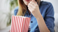Happy woman eating popcorn and watching tv at home Stock Footage