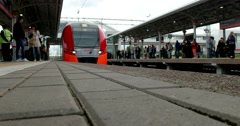 Red train arrives at the station, passengers exit and enter the car Stock Footage