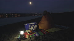 Man Wraps Himself In Sleeping Bag, And Looks Out At Pretty Water View Stock Footage