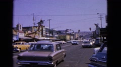 1963: vintage cars driving on a four lane road with mountains in the background Stock Footage