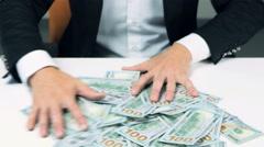 Greedy unrecognizable businessman hands grabbing lot of hundred dollar bills Stock Footage