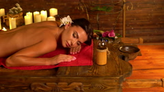 Young woman lying on wooden spa bed in massage spa salon.4k Stock Footage