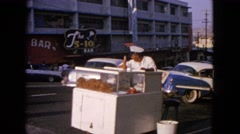1963: street food seller watching cars passing by while two white men cross the Stock Footage