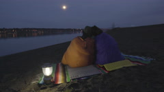 Couple Sit On A Riverbank, Wrapped In Sleeping Bags, Enjoy The View Of River Stock Footage