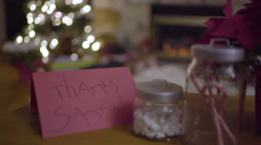 Closeup Of Thank You Card To Santa, Kids In Background Snuggled Up By Fire Stock Footage