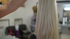 Hairdresser combing hair blond wig Stock Footage