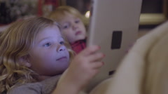 Closeup Of Little Kids Watching A Video On A Tablet By A Cozy Fireplace Stock Footage