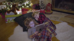 Siblings Snuggle Up Under Tree And Watch A Christmas Show On A Tablet Stock Footage