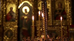 Burning candles in front of the iconostasis in the Orthodox Church Stock Footage