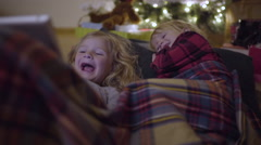 Kids Snuggle Up Under Christmas Tree And Watch A Funny Video On Tablet Stock Footage