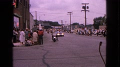 1963: a festive parade with a marching band and crowds gathered on either side Stock Footage
