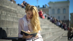 Young woman puts aside the laptop and picks up a book on the stairs in the cente Stock Footage