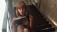 Girl in mini skirt reads a interesting book while sitting on the stairs Stock Footage