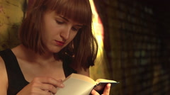 Girl in mini skirt reads a book and standing near graffiti wall close-up Stock Footage