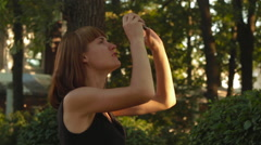Beautiful girl shoot video on smartphone at the city park with sunlight Stock Footage