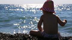 Little baby in panama playing on the beach on a background of blue sea and Stock Footage