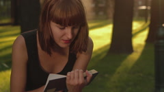 Cute girl reads a interesting book and sitting at the city park close-up Stock Footage