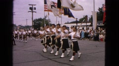 1963: a large group of men in kilts marching through the street playing  Stock Footage