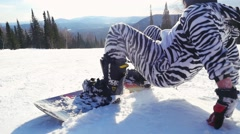 Snowboarder man in suit of kigurumi of zebra jumping and going in high mountains Stock Footage