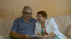 Beautiful elderly couple looking photos on your tablet Stock Footage